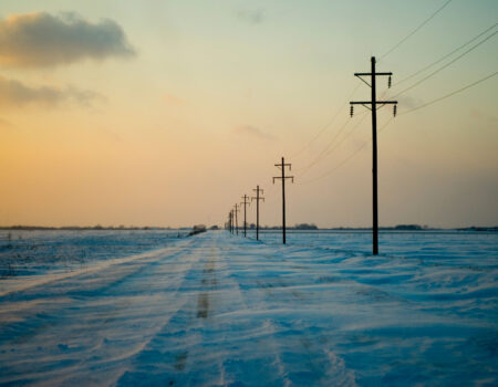 BR4DFR Telephone poles line an empty snow-covered dirt road Mount Pleasant, Iowa on January 4th, 2008.
