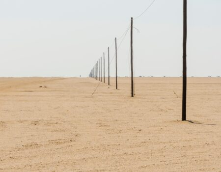 W7GF0T Telegraph poles beside a road stretch out as far as you can see, showing the curvature of the earth.  Namib Desert, Namibia
